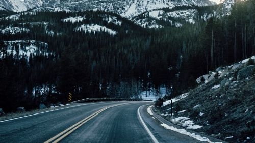 Driving through mountains covered in snow HD Wallpaper